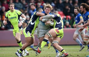 Jared Saunders of Saracens is tackled by Johnny Leota