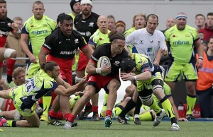 Mike Ellery (C) of Saracens drives through the Sale Sharks defence
