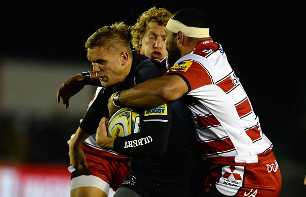 Chris Harris (L) of Newcastle Falcons tackled by John Afoa (R) and Billy Twelvetrees
