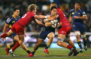 Christian Lealiifano of the Brumbies is tackled by the Reds