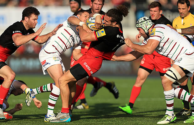 Mike Ellery of Saracens is tackled by Fergus Mulchrone and Chris Noakes of London Irish