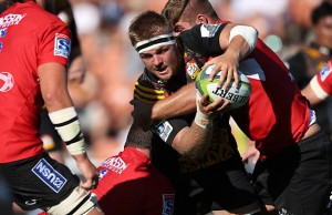 Sam Cane gets wrapped up by the Lions defence